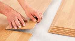 Pair of hands laying flooring
